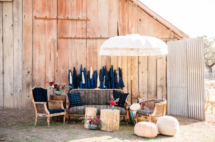 Look at this outdoor lounge zone with oversized tassel backdrop and boho touches, it's amazing