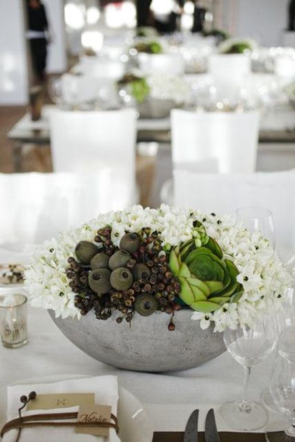 concrete bowl with various flowers and fruit as a wedding centerpiece
