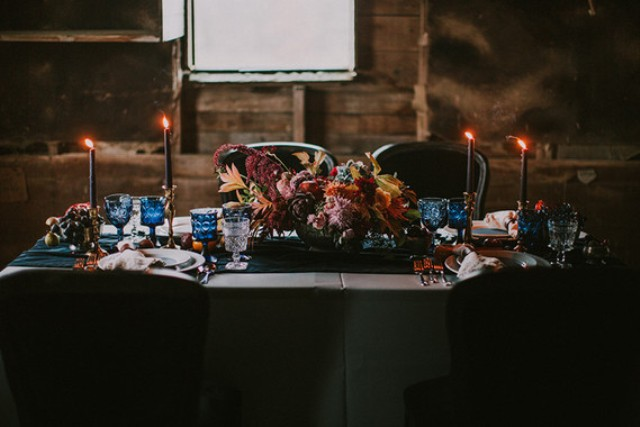Black candles, blue glasses and a lush moody floral and leaf centerpiece rocked this table setting