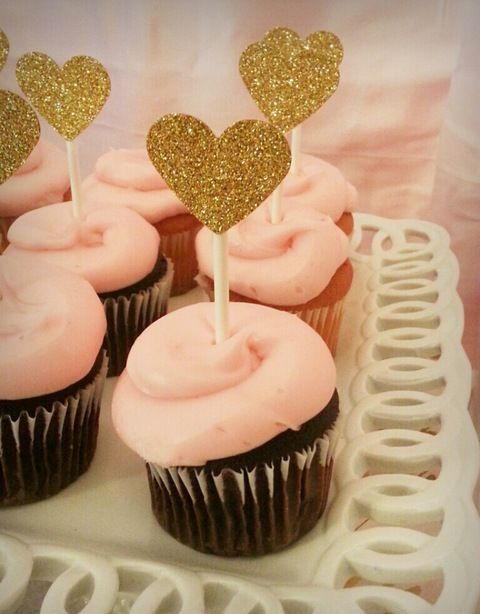 chocolate cupcakes with pink glazing and gold glitter heart toppers