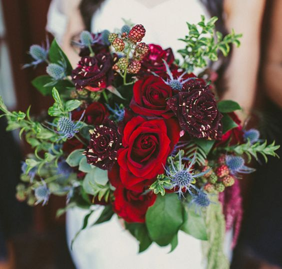 winter-inspired bouquet with dark red roses and blue thistle