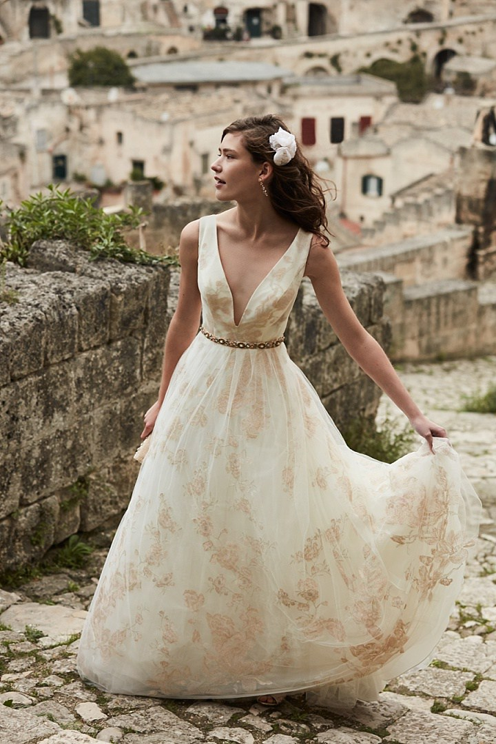 Lily gown is with gold and blush embroidered cherry blossoms cascade from shoulder to hem with a soft net overlay for added dimension, a plunging neckline, totally sheer back