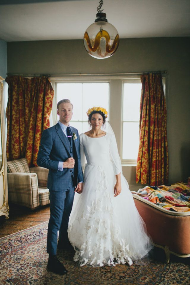 The groom was wearing a slate grey or blue suit with a shirt and a tie, it was a vintage-inspired look