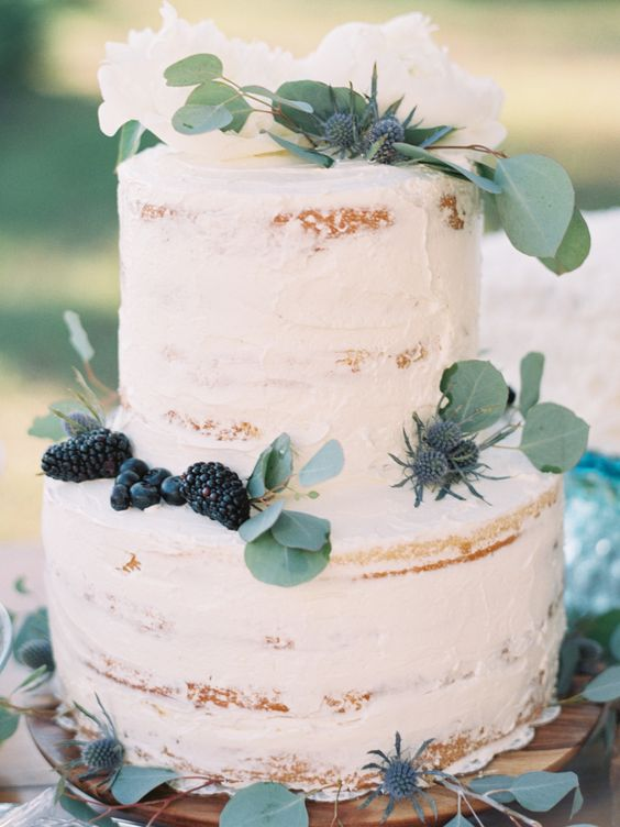 two-tiered cake topped with greenery, blackberries and thistles