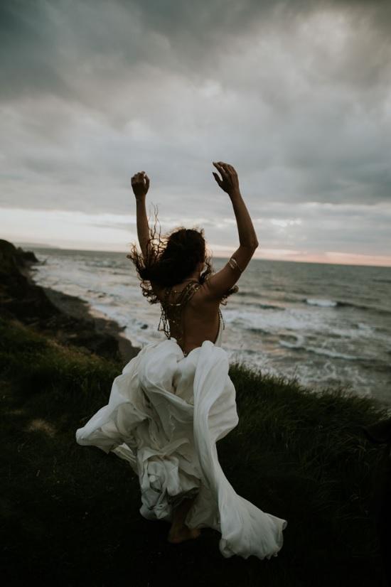 The bride standing outside and enjoying fresh seaside breeze