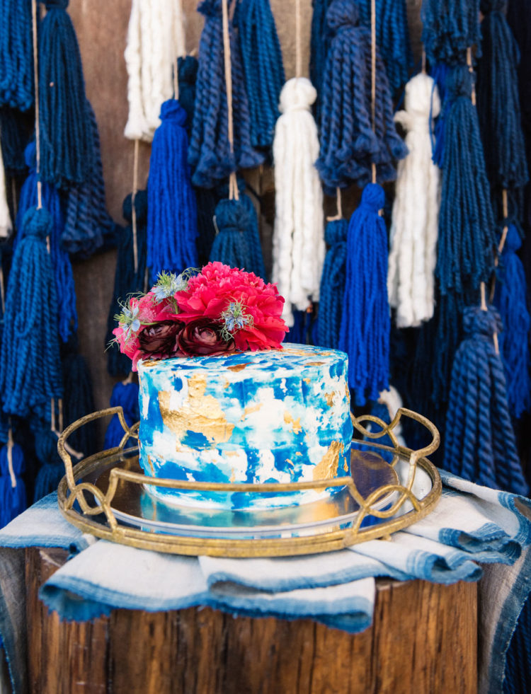 The cake is a masterpiece covered with indigo and edible gold, with bold fuchsia flowers on top