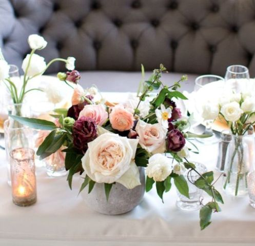 concrete vases contrast with the delicate floral centerpiece