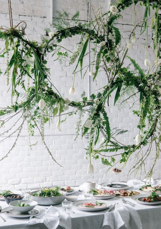 decorated with fern leaves and vines, these hanging centerpieces bring a little vibrancy to a minimalist tablescape