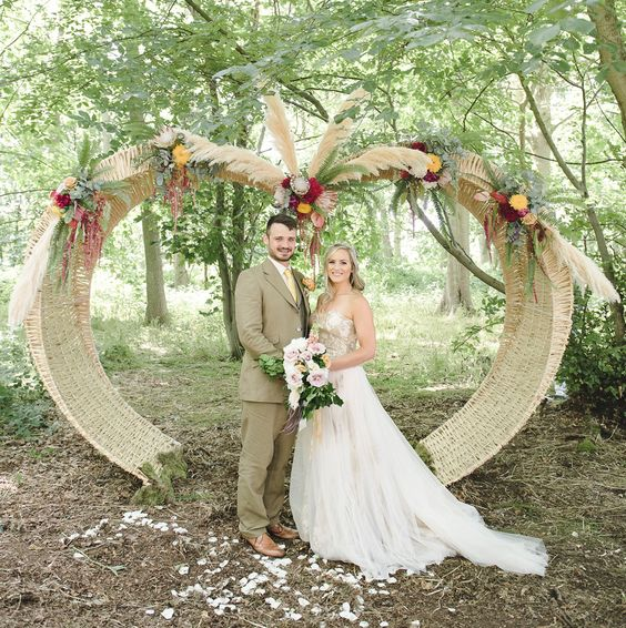 woven wedding arch with bold flowers and pampas