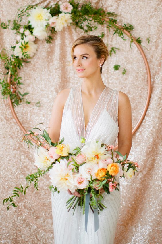 copper hoop with greenery and flowers as a wedding backdrop