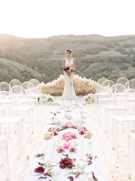 pampas altar, lucite chairs and a flower covered aisle for a boho ceremony