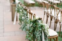 12 aisle chairs decorated with eucalyptus and ribbons