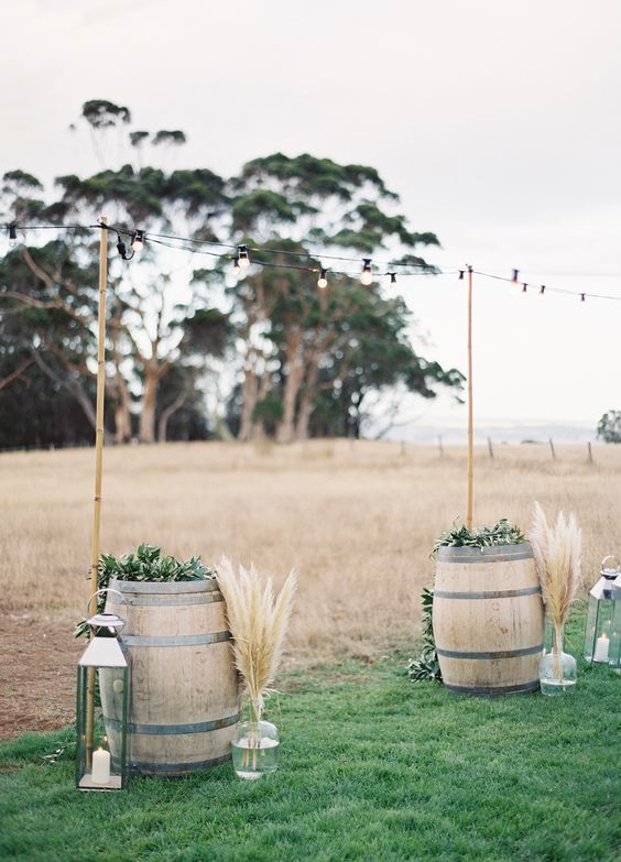 wedding altar with wine barrels, lanterns and pampas in bottles
