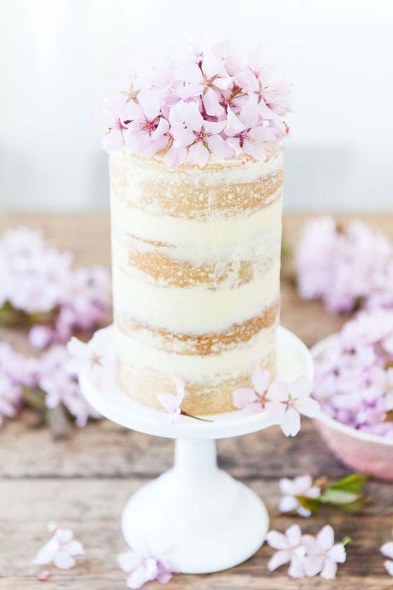 individual semi naked wedding cake with cherry blossom on top
