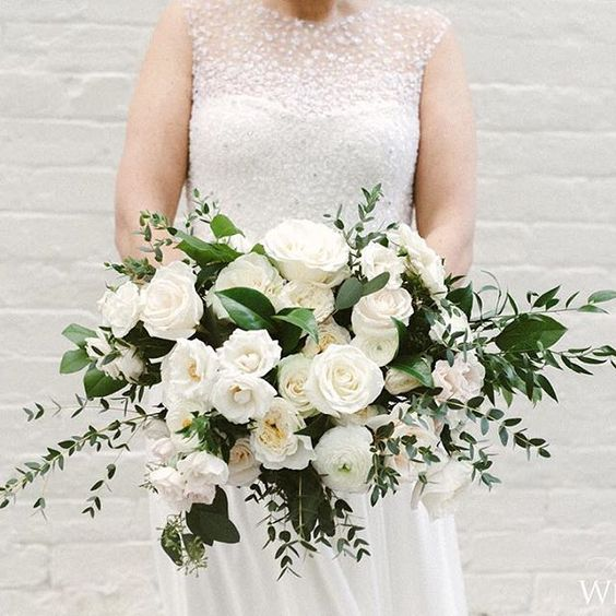 white and green bouquet of roses, ranunculus, ruscus, and salal