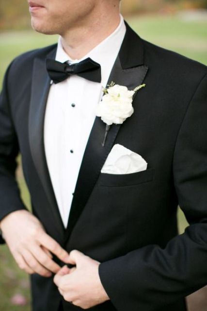elegant black tuxedo with a white flower boutonniere