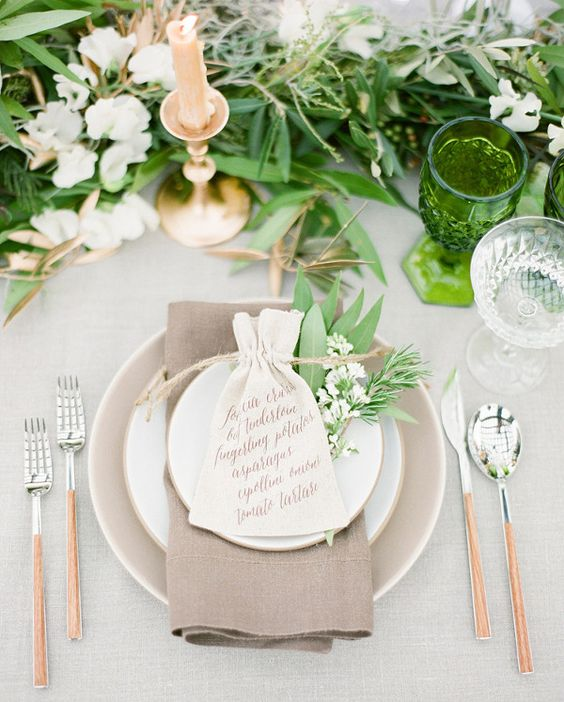 fresh neutral spring table setting with a lot of greenery and flowers