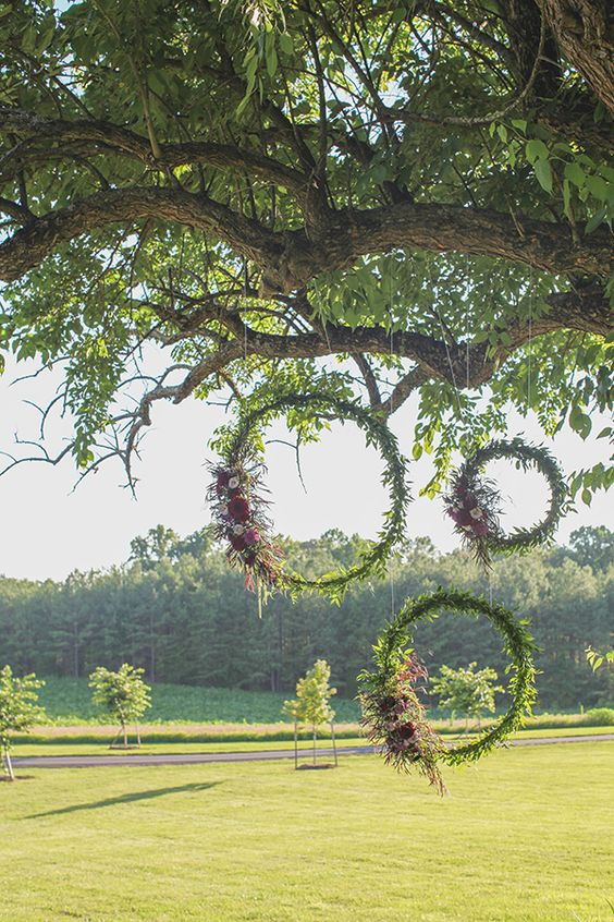 moss, greenery and flower covered hoops for outdoor wedding backdrop