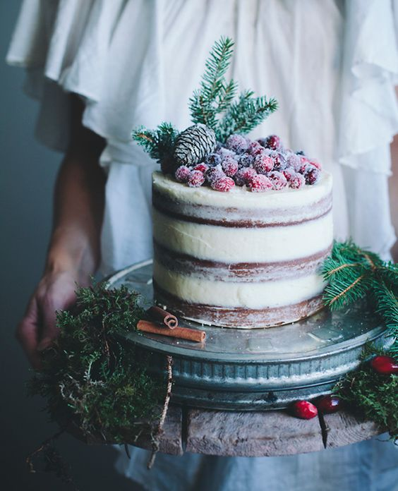 semi naked wedidng cake with sugared berries, evergreens and a pinecone