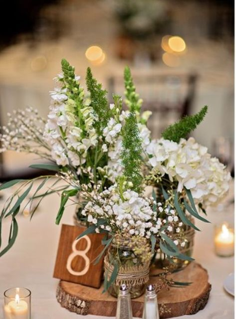 wood slice with several mason jars as vases and a wooden table number