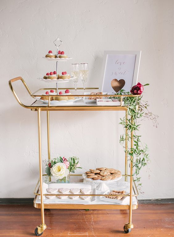 brass dessert cart with fresh greenery, champagne and an art piece