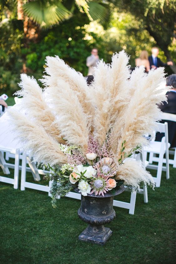 an antique urn with pampas grass and flowers