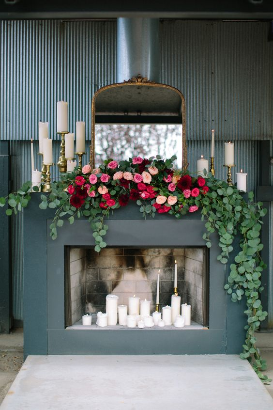 faux fireplace decorated with candles, eucalyptus garlands and bold florals