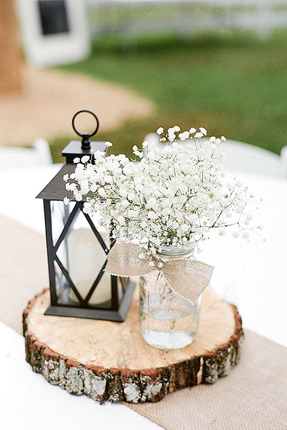 stylish centerpiece with a candle lantern and a mason jar with baby's breath