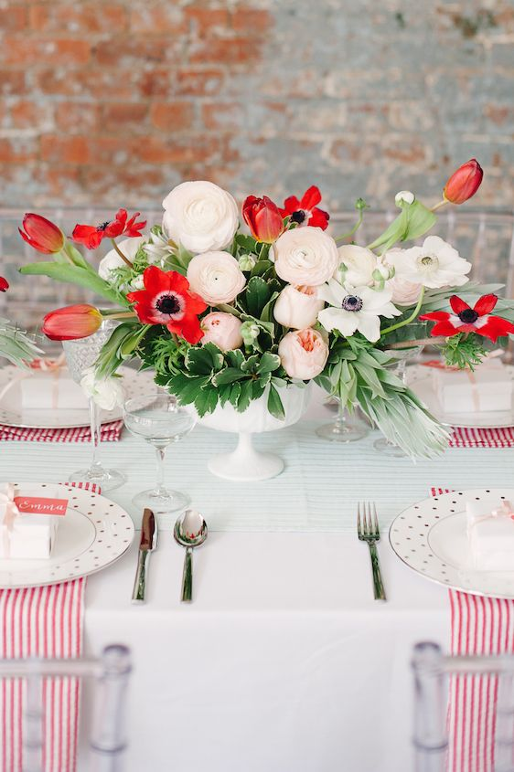 white table with red stripes and a red and white floral centerpiece