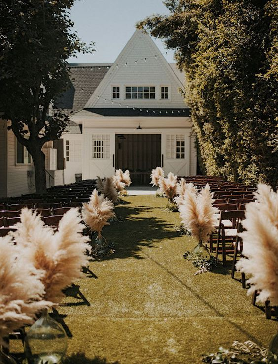 backyard wedding aisle decorated with pampas in large sheer vases