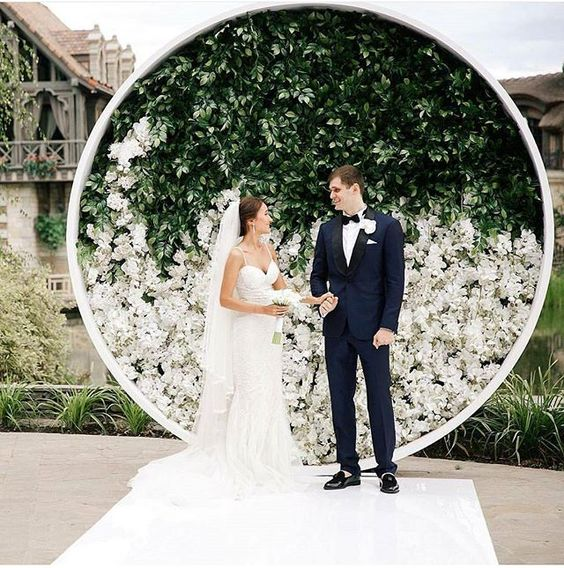 circular backdrop adorned with greenery and white hued bloom which will set a modern and elegant wedding statement