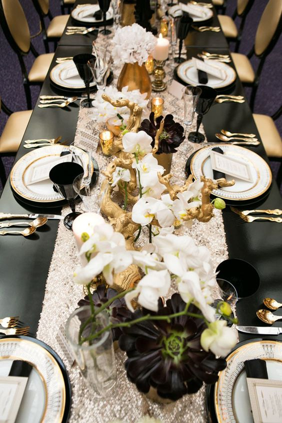 lush black, white and gold table decor with lots of florals and gilded driftwood