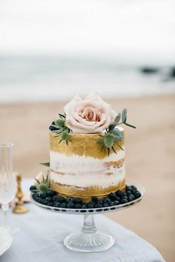 semi naked gold painted wedding cake with blueberry, thistle and a rose