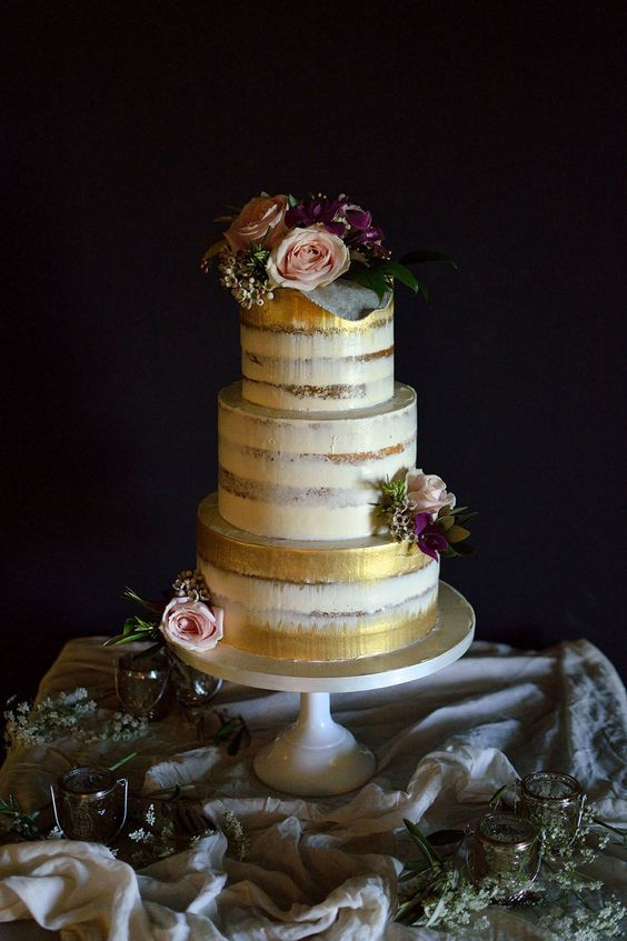 gold-brushed semi-naked wedding cake with flowers