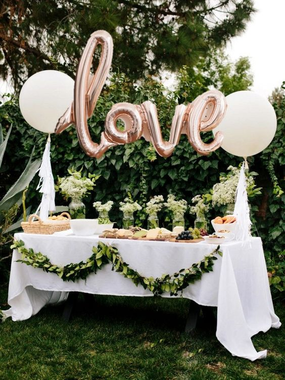 outdoor dessert table with pink balloons and greenery