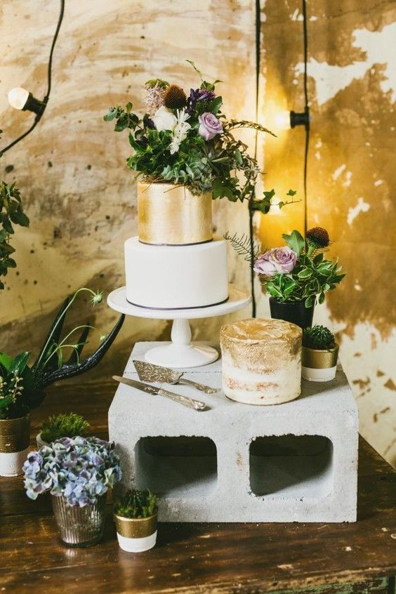 simple concrete cake stand creates a perfect contrast with refined gold cakes