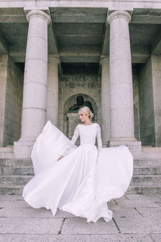 long sleeve wedding dress with a lace bodice and a flowy plain skirt