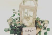 24 a wood slice, eucalyptus and a candle lantern can make up a great centerpiece