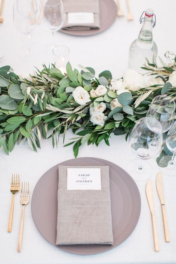 cream-colored wedding tablescape with a greenery and flower runner and a grey place setting