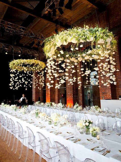 hoops covered with lush greenery adn florals as wedding chandeliers