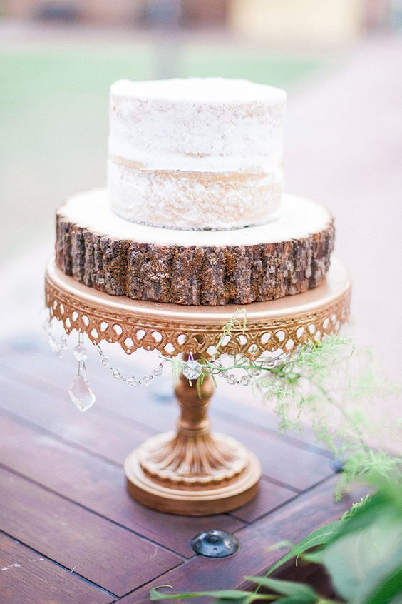 vintage cake stand with an additional wood slice and a semi-naked wedding cake