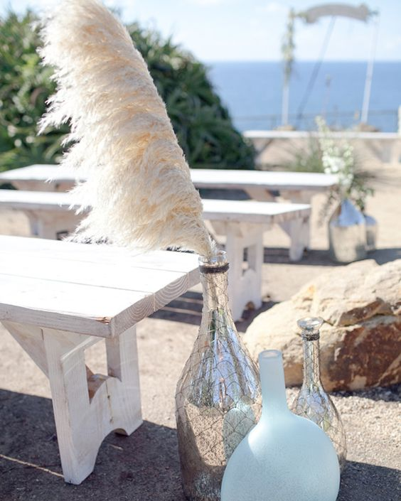 beach wedding aisle with pampas grass in mercury glass bottles