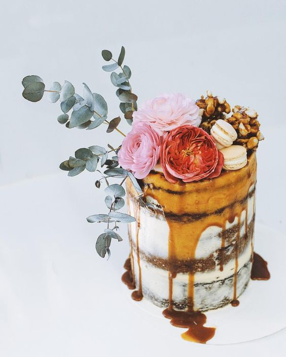 layers of salted caramel, chocolate brownie and raspberry flourless cake topped with flowers and greenery