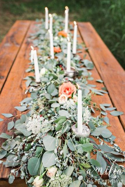eucalyptus garland with peachy flowers and candles