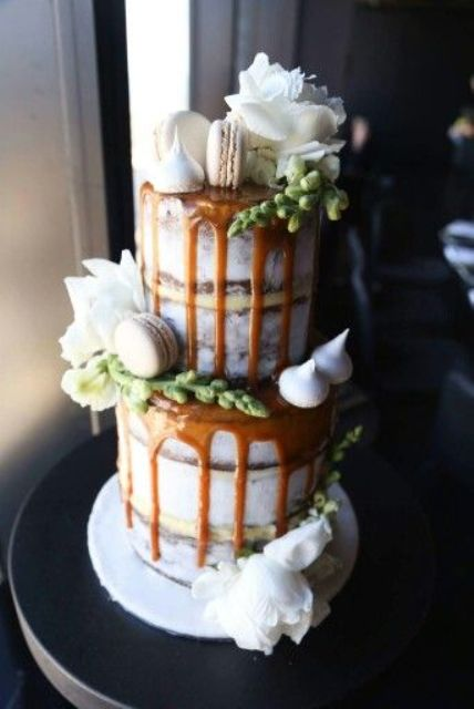 salted caramel drip wedding cake topped with macarons and meringues