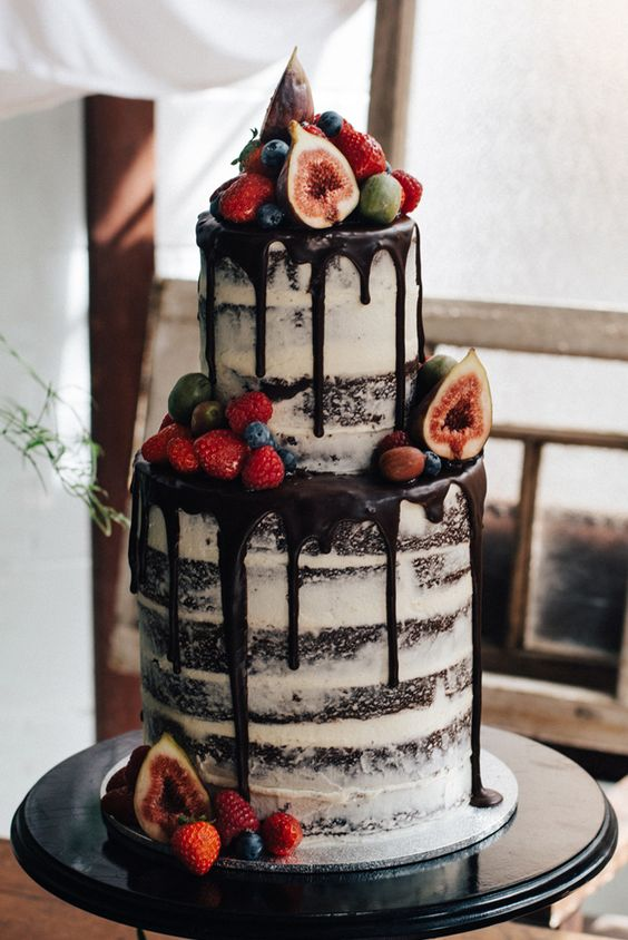 semi naked chocolate wedding cake with chocolate drizzle and fresh berries