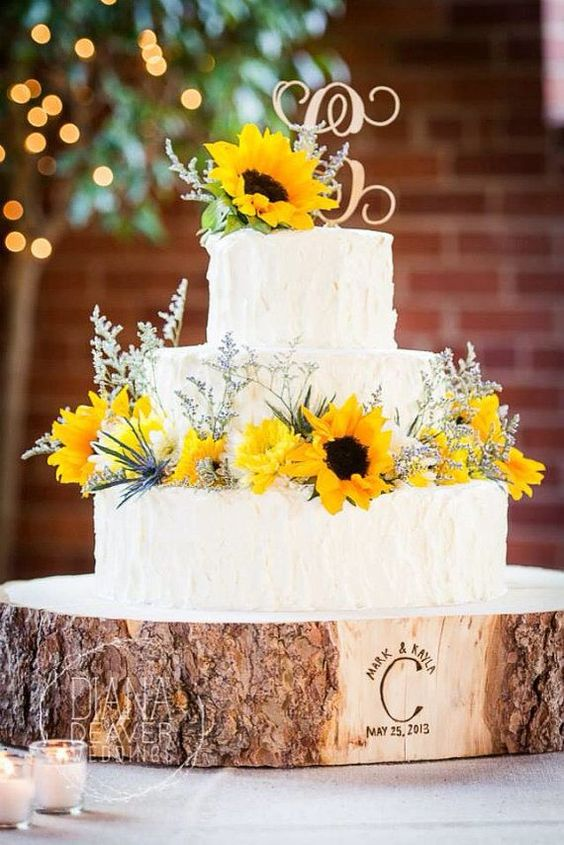 sunflower wedding cake displayed on a wood slice with the wedding date