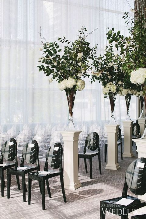 modern chic aisle decor with black chairs and textural greenery and flower compositions