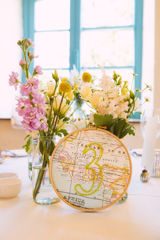 travel-inspired table numbders in embroidery hoops