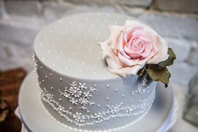 dove grey one-tier lace wedding cake topped with a flower